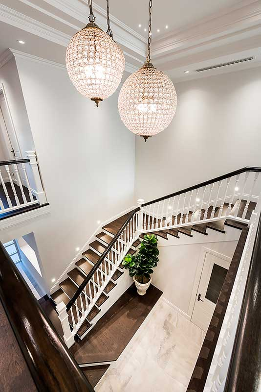 Grand staircase leading to foyer with chandeliers