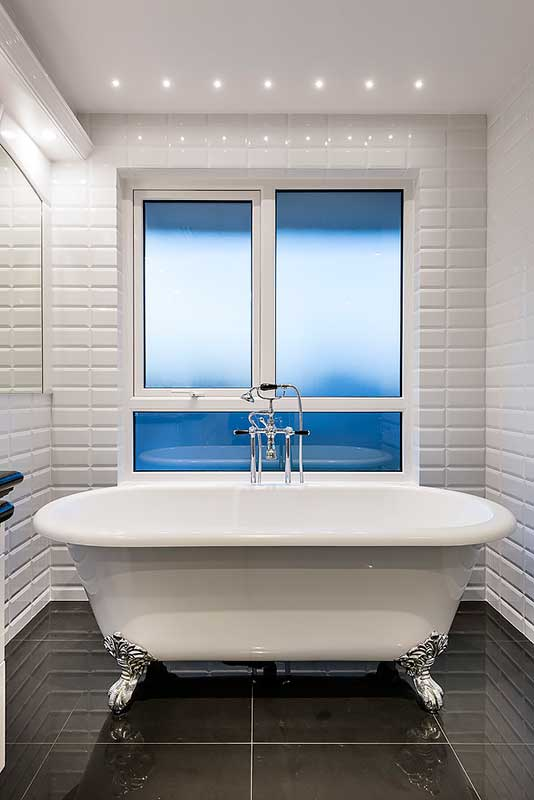 Elegant clawfoot bath tub in Hamptons style bathroom